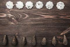 Brown wood background with pronounced texture. With golden cones and sweet biscuits arranged diametrically opposed. Space for a greeting message. Top View Royalty Free Stock Photography