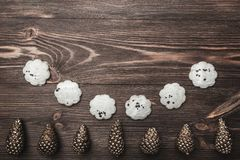 Brown wood background with pronounced texture. With golden cones and sweet biscuits at the bottom of the picture. Space for a greeting message. Top View Stock Photography