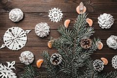 Brown wood background. Slice of mandarins. Fir tree and cones. Sweets. Christmas and New Year decorations. Xmas and Happy New Year composition. Flat lay, top Royalty Free Stock Image