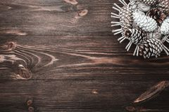 Brown wood background with texture. Decorative fir cones.  Space for Santa`s message and holidays. Minimalist style. Holiday card. Xmas and Happy New Year Stock Photography