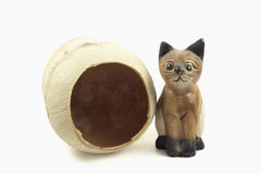 Brown wood cat statue and coconut shell isolated on white backgr Stock Photos