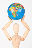 Brown wood mannequin holding concerned a globe protect Royalty Free Stock Image