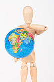 Brown wood mannequin holding concerned a globe protect Stock Image