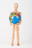 Brown wood mannequin holding concerned a globe protect Royalty Free Stock Photos