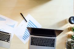 Brown wood office desk table with a paper work, pen, cactus, clo stock photography