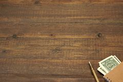 Brown Wood Table With Notebook, Money  And Gold Ink Pen Royalty Free Stock Images