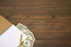 Brown Wood Table With Notebook, Money  And Gold Ink Pen Royalty Free Stock Photography