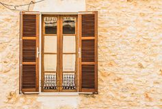 Brown wood window with open shutters and rustic stone wall background Royalty Free Stock Photo