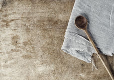 Brown wooden background with a wooden spoon and a gray tableclot. H, empty space on the left Stock Photography