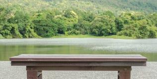 Brown wooden benc. H at a green lake Stock Photos