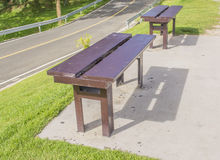 Brown wooden  bench aside the road in day time Stock Photography