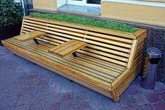 Brown wooden bench with decorative grass near the house wall Stock Photos