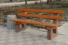 Brown wooden bench and a gray urn on the sidewalk in the park stock images
