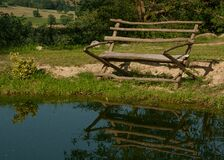 Brown Wooden Bench on Green Grass Near on Body of Water Stock Photos
