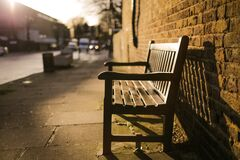 Brown Wooden Bench on the Side of the Road Royalty Free Stock Images