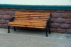 Brown wooden bench on a sidewalk near a stone wall Stock Images