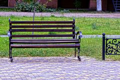 Brown wooden bench on the sidewalk in the park Stock Photo