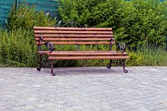 Empty wooden bench of brown color on the sidewalk near the lawn Stock Images