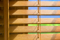 Brown wooden blinds that are slighlty open. Showing blue sky on a bright sunny day Stock Photography