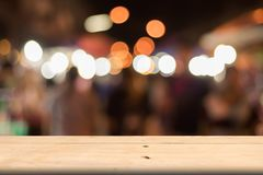 Brown wooden board of blank on front, blurred people walking. On night market background, copy space for presentation Stock Images