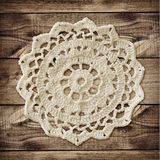 Brown wooden board and crochet doily. For background. Flat lay. Top view Stock Image
