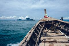 Brown Wooden Boat on Sea Overlooking Rocky Island Stock Images