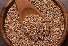 Brown wooden bowl full of buckwheat Royalty Free Stock Images