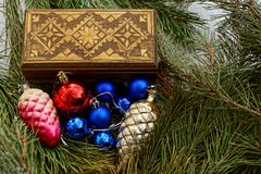 Brown wooden box and Christmas toys in pine branches Royalty Free Stock Images