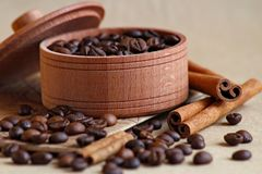 wooden box with coffee beans, and cinnamon sticks on a beige background. stock photos