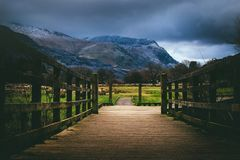 Brown Wooden Bridge Near Mountain at Daytime Stock Photo