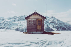Brown Wooden Bunk House Surrounded by Snow Covered Ground and Mountains during Daytime Royalty Free Stock Photography