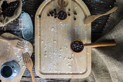 The brown wooden chopping board and Coffee beans. With flour on a rustic table,top view Royalty Free Stock Photography