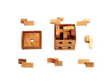Brown wooden cube (puzzle) with wooden pieces scattered around. Isolated on white Stock Photos