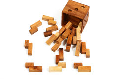 Brown wooden cube (puzzle) with wooden pieces scattered around on white. Background as a metaphor for intelligence Royalty Free Stock Photo