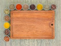 Brown wooden cutting board and many glass jars with spices left and above of it on a background of a rough green mat made of. Natural plant fibers. Cooking copy stock photos