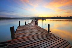Brown Wooden Dock on Calm Body of Water Surrounded by Silhouette of Trees during Sunset Stock Images