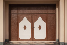 Brown wooden door with artistic carvings on them Royalty Free Stock Images
