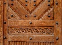 Brown wooden door with metal rivets Royalty Free Stock Images