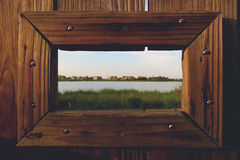 Brown Wooden Door With Rectangular Hole Showing Green Grass Near Body of Water Royalty Free Stock Images