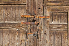 Brown wooden door with rusty handles and locks. Old brown wooden door with rusty handles and locks royalty free stock photo