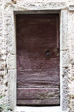 Brown wooden door in a stone wall close-up of  village house. Italy . Royalty Free Stock Photos