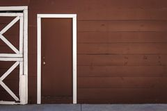 Brown wooden door with white frame stock photography