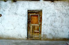 Brown Wooden Door in White Painted Wall Stock Photography