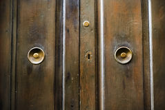 Brown wooden doors with metal handles of an unusual form Royalty Free Stock Images