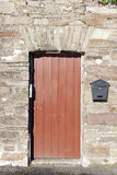 Brown wooden doorway and a post box Royalty Free Stock Photography