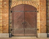 Brown wooden double doors with a red brick arch. stock image
