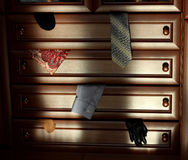 Brown wooden dresser lit by the sun. Pieces of clothing in opened drawers. The image of brown wooden dresser. Pieces of clothing in opened drawers Royalty Free Stock Photography
