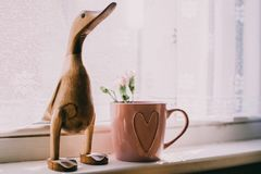 Brown Wooden Duck Figurine Near Brown Ceramic Mug Stock Images