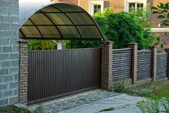 Brown wooden fence and closed gates with a private house near the road Stock Image