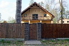 A brown wooden fence and a closed door and part of a large house. A brown wooden fence near the road and a closed door and part of a large house Royalty Free Stock Images